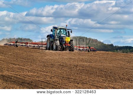 A Blue Tractor Sows Grain. Farm Work On A Farm In The Czech Republic. Tractor On A Wheat Field. Agri