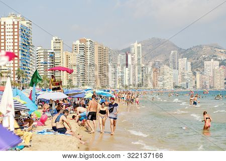 Benidorm, Spain - July 26, 2019: Lot Of Holidaymakers Enjoy Summer Holidays On Sandy Beach Of Benido
