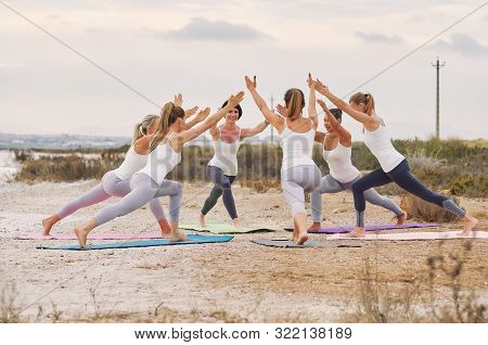 Group Of Slim Attractive Women Wearing Sportswear Doing Yoga Standing On Mats In Circle Outdoors On