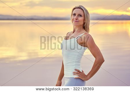 Attractive Woman In Sportswear Pose Against Cloudy Bright Sky At Sunset Looking At Camera Standing O