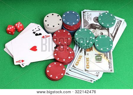 Cards and paper dollars on a table with green cloth