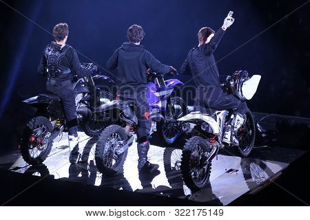 Back View Of Three Motorcross Racers /winners On Stage