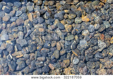 Texture Of Wet Pebbles. Smooth Pebbles Under Clear Water. Striped Stones At The Bottom Underwater Cr