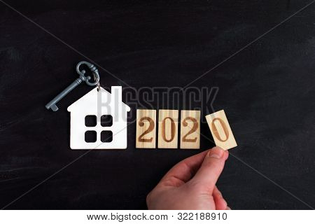 Model Of A House With A Key Next To The Number 2020 And A Hand / Build Individual Housing In The New