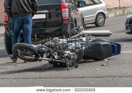 Broken Motorcycle Closeup Beside The Car. An Accident On The Road In The City On A Sunny Day Involvi