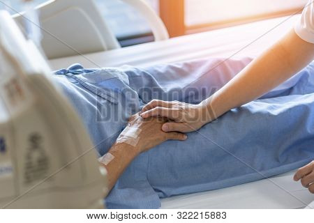 Caregiver Holding Elderly Senior Patient (ageing Old Adult Person) Hand In Hospital Bed Or Nursing H