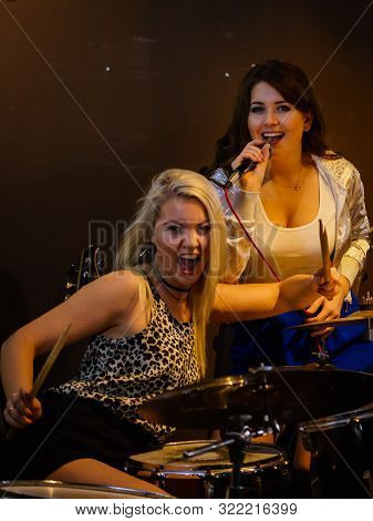 Woman Singing While Rest Of The Band Playing Instruments, Performing On Stage. Female Musicians: Dru