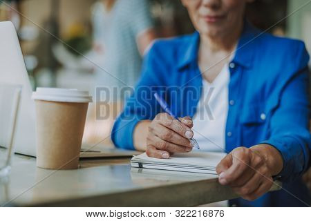 Woman At The Table Making Notes In Notebook Stock Photo