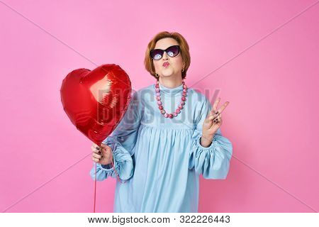 Lovely Funky Old Woman Blows A Kiss. Elderly People. An Outpost For Dating Sites, A Wedding Agency.