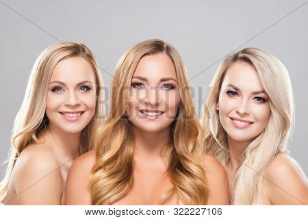 Studio portrait of young, beautiful and natural blond women over grey background. Close-up of smiling girls. Face lifting, plastic surgery, cosmetics and make-up.