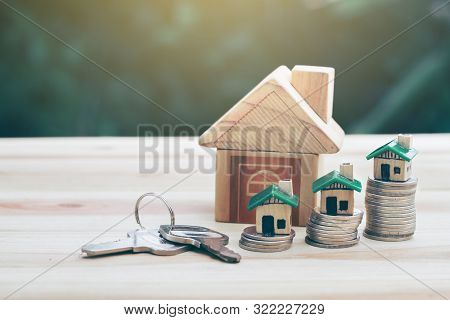 House Placed On Coins. Houses, Keys Placed On A Wooden Table.  Planning Savings Money Of Coins To Bu