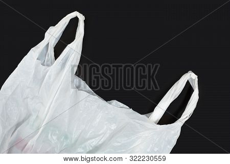 White Plastic Bag On Black Background. A White Plastic Bag Texture, Macro, Background. Reduction Of