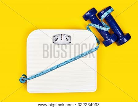 Bathroom Scales And Measuring Tape For Weight Loss Concept On Yellow Background. Sport And Diet For