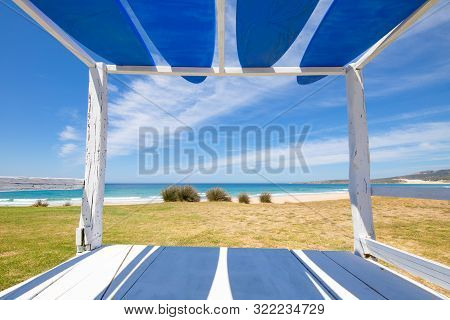 Bolonia Beach Framed From A Wooden Bed With Surf Boards