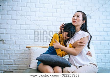 Asian Mother Comforting Crying Teenage Daughter In Miserable, Stressed, Depressed, Sad State Of Mind