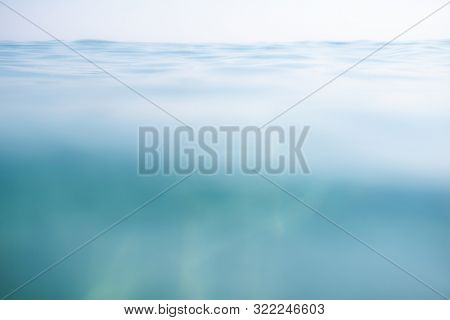 Blue calm sea with waves and rays of sunlight shining through, on the water surface and underwater. Ocean. Tranquility and silence. Beautiful natural background, wallpaper