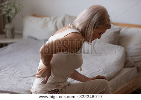 Upset Mature Woman Suffering From Backache, Rubbing Stiff Muscles