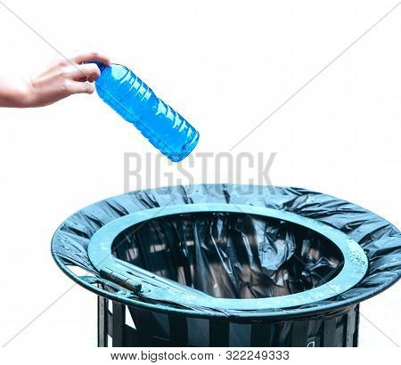 Caucasian Hand Throwing A Bottle Of Water Made Of Blue Plastic Into A Wastepaper Basket.