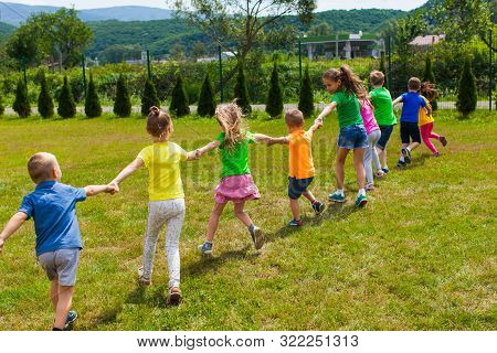 Children Play Holding Hands On The Green Grass, Back View