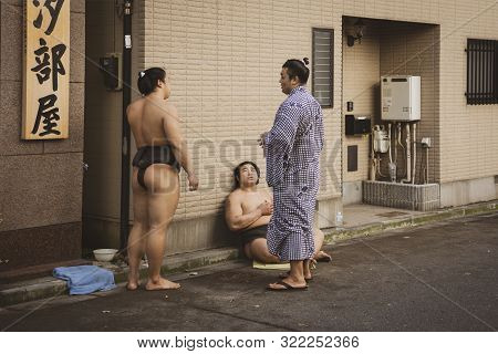 Tokyo, Japan - October 7, 2018. Japanese Sumo Wrestlers Are Resting And Talking On A Street After Tr