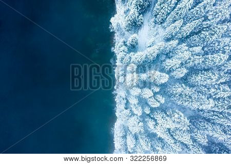 Winter Background. Christmas Nature. Snowy Forest At Blue Lake. Aerial View. From Above. Winter Land