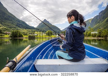 Woman fishing on Fishing rod spinning in Norway. Fishing in Norway is a way to embrace the local lifestyle. Countless lakes and rivers and an extensive coastline means outstanding opportunities...