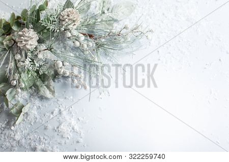 Christmas and New Year holidays concept with snowy fir branches and pine cone on light background. Christmas greeting card, top view.