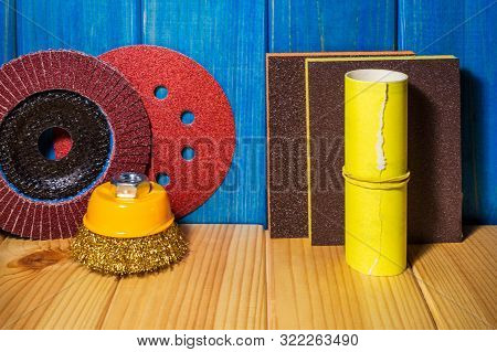 Set of abrasive tools and sandpaper on blue wood background poster