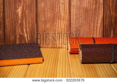 Set of abrasive tools and sandpaper on brown wood background poster