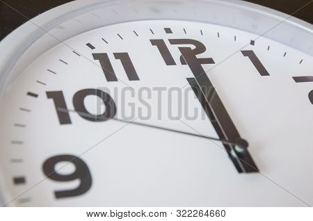 Macro Photo Of A Black And White Clock From 12 O'clock. Time Concept