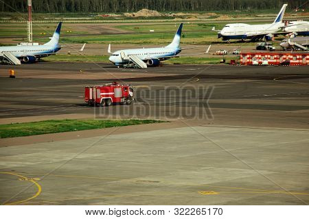 Fire Truck On The Runway Near The Aircraft. Airport Rescue Service. Firefighters And Fire Department