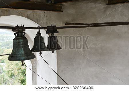 Wind-bell with metal fish at the traditional temple. wind-shaking wind chime. Bells in the temple. Bells in an old temple or cathedral against a white wall and a partial view from the windows poster