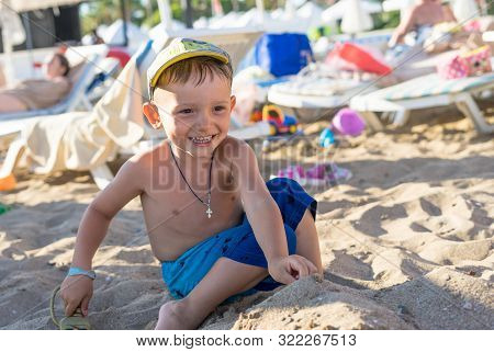 Young Boy Playing In The Sand And Waves On The Beach. Happy Family Lifestyle.