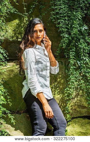 poster of Young Beautiful East Indian American Woman with long hair traveling in New York City, wearing white long sleeve shirt, standing by rocks with long green leaves at Central Park, talking on cell phone.