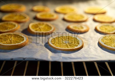 Oranges Drying In The Oven On A Metal Rack And Baking Paper. Selective Focus On Dried Orange. Close