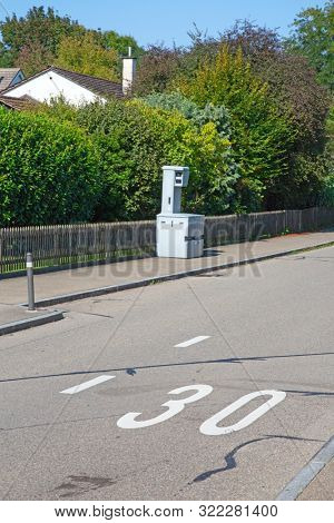 Speed camera on the narrow street of small swiss city. The 30 km/h is typical limit in the living zones in Switzerland