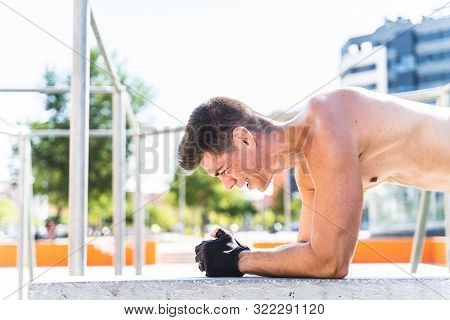 Young Man Doing Street Workout Outdoors. Man Doing Puss-Ups in the Street. Guy Training in the Street.. Latin American Man Exercising Outdoors. Sport Concept. poster