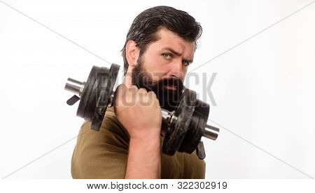 Serious Man With Dumbbell During An Exercise. Man With Dumbbell In Gym. Bearded Man Working Out With