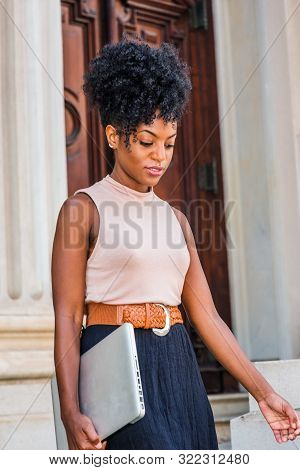 Walking And Thinking. Young Black Woman With Afro Hairstyle, Wearing Sleeveless Light Color Top, Bla