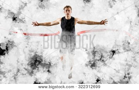 Runner wins by crossing the finish line.  Strong athletic man, running on white smoke background wearing in sportswear. Sport and fitness motivation