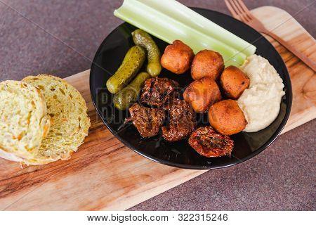 Raw Veggies Falafels And Hummus On Cutting Board With Corn Bread