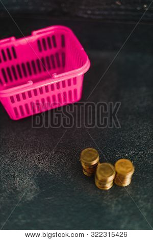 Pink Shopping Basket Next To Stacked Coin Piles