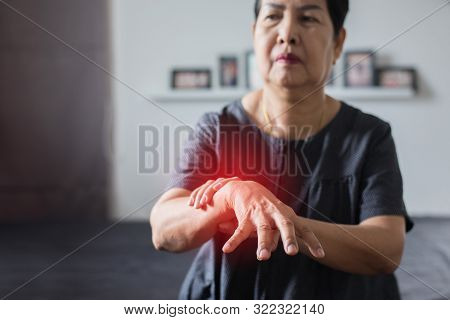 Elderly Woman Suffering With Parkinson Disease Symptoms On Hand While Standing On White Background