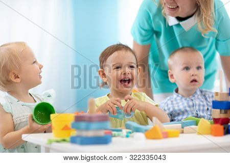 Happy Babies In Day Care. Group Of Kids Playing Toys With Kindergarten Teacher. Children Lesson In C