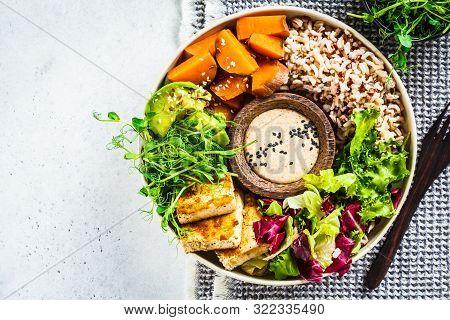 Buddha Bowl With Tofu, Avocado, Rice, Seedlings, Sweet Potato And Tahini Dressing. Vegan Food Concep