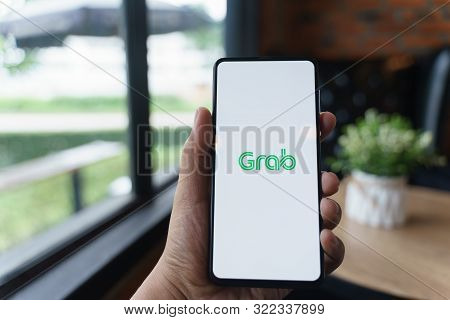 Chiang Mai, Thailand - Aug.24,2019: Man Holding Xiaomi Mi Mix 3 With Grab Apps On Screen. Grab Is Sm