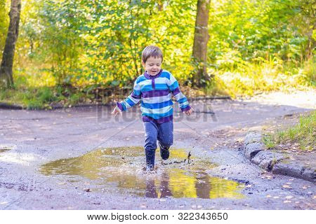 A Little Boy Is Jumping In A Puddle. A Boy In Rubber Boots. Happy Childhood. Puddles After The Rain.