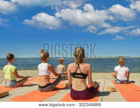 Group Young Woman's Yoga Practice Relaxation In-class Exercise On The Beach And Seaside.
