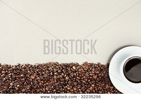 White coffee cup with coffee beans and white background seen from above