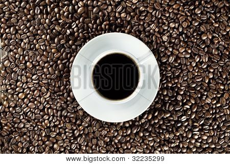 White coffee cup on coffee beans seen from above